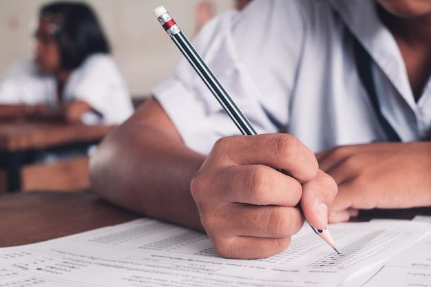 Examen con estudiante de la escuela uniforme haciendo prueba educativa con estrés en el aula Foto Premium