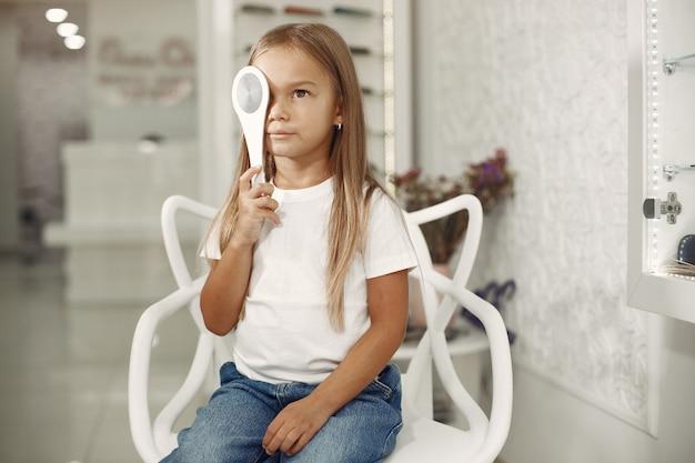Examen y examen de la vista para niños. niña con chequeo ocular, con foróptero. examen de la vista para niños Foto gratis