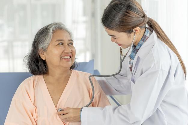 Examen médico senior paciente femenino de edad avanzada en pacientes en cama de hospital - concepto senior médico y sanitario Foto gratis