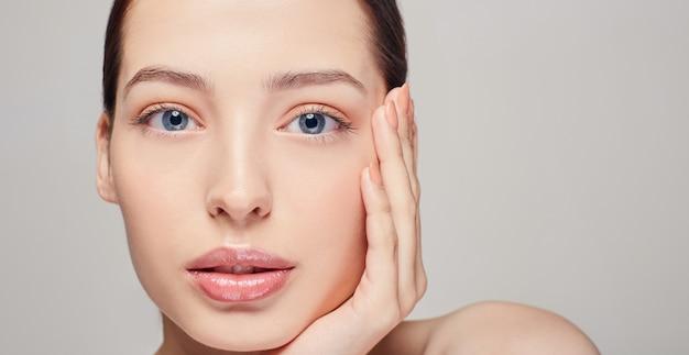 Una excelente chica hermosa y sofisticada con labios, cabello oscuro y piel radiante, delicada y limpia en el gris. lady puso su cabeza sobre su mano. se ve derecho. cosmetología Foto Premium
