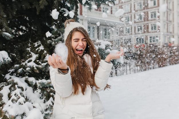 Excitada imagen brillante de mujer de invierno bonita increíble alegre divirtiéndose con nieve al aire libre en la calle. momentos felices, jugar con copos de nieve, disfrutar, emociones positivas. Foto gratis