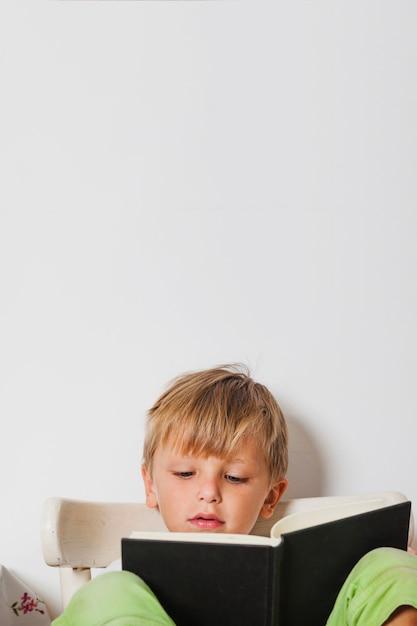Excited boy reading book Foto gratis