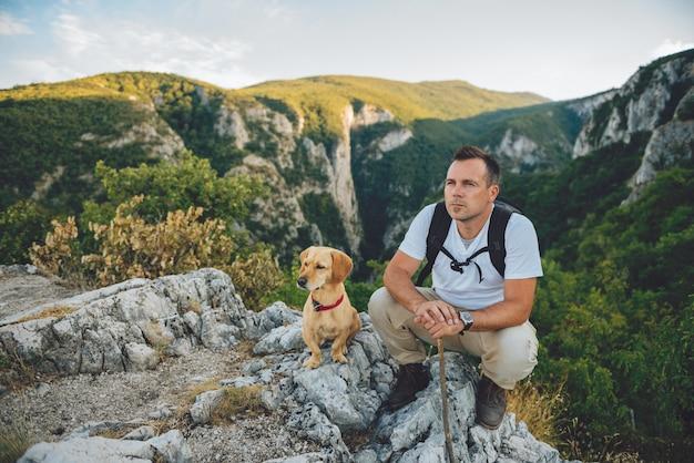 Excursionista y su perro sentado en la cima de la montaña Foto Premium