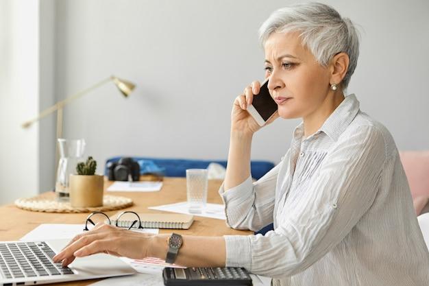 Exitosa empresaria madura confiada con el pelo corto gris que trabaja en el elegante interior de la oficina, usando una computadora portátil y una calculadora, hablando con un socio comercial a través de un teléfono celular. personas, edad y ocupación Foto gratis