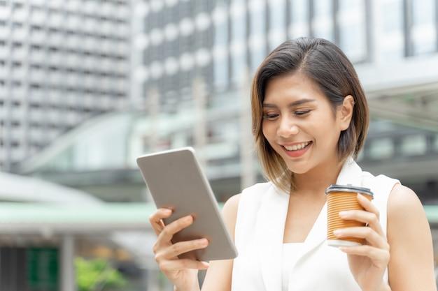 Exitosa hermosa mujer de negocios asiática joven usando teléfono inteligente y una taza de café en la mano Foto gratis