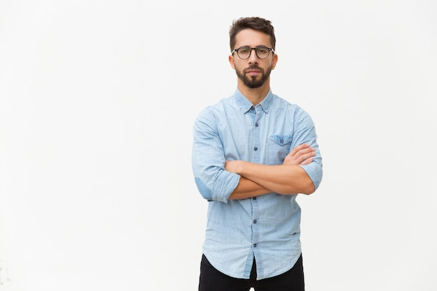 Exitoso empresario masculino confiado posando con los brazos cruzados Foto gratis