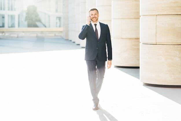 Exitoso empresario masculino en ropa formal, hace una llamada telefónica a su pareja a través del teléfono móvil Foto Premium