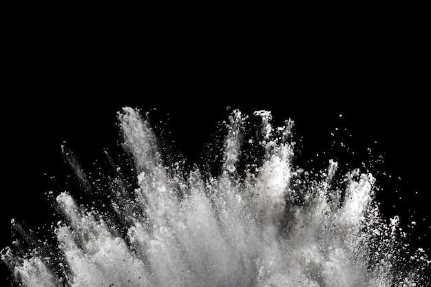 Explosión de polvo blanco sobre negro. Foto Premium