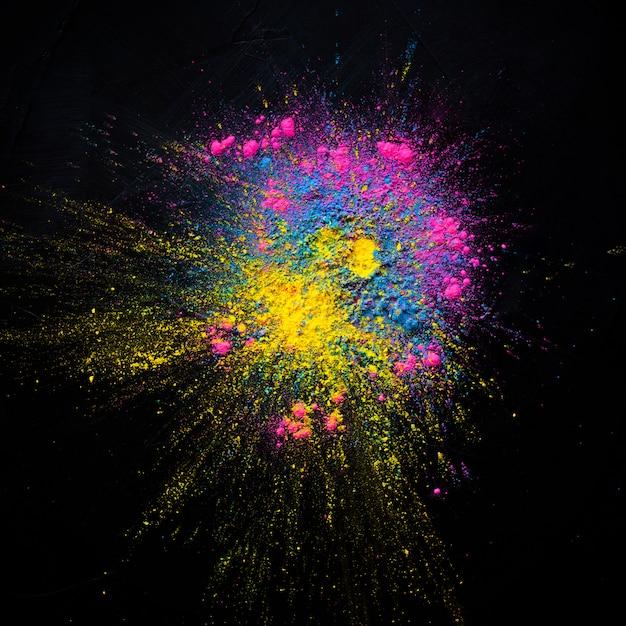 Explosión de polvo coloreada extracto en un fondo negro. polvo abstracto salpicado de fondo, Foto gratis