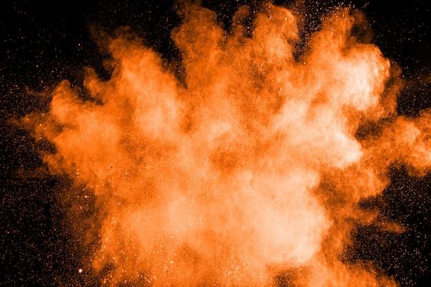 Explosión de polvo naranja abstracto. congelar el movimiento de polvo naranja salpicaduras. Foto Premium
