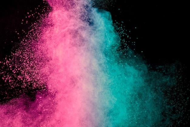 Explosión rosa y azul de polvo de maquillaje sobre fondo oscuro Foto gratis