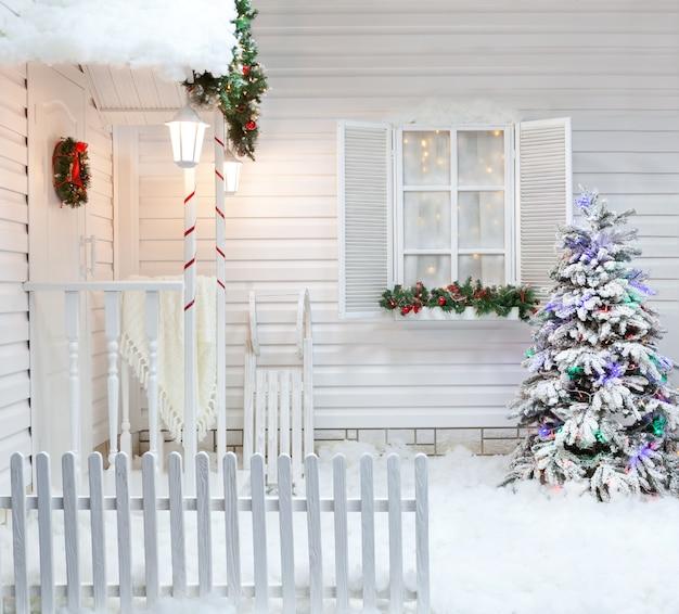 Exterior de invierno de una casa de campo con adornos navideños al estilo americano. Foto Premium
