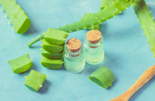 Extracto de aloe vera en una pequeña botella y piezas sobre la mesa. enfoque selectivo Foto Premium