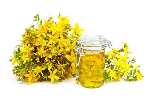 Extracto de hierba de san juan en botella de vidrio y rama de flores amarillas frescas aisladas en blanco Foto Premium