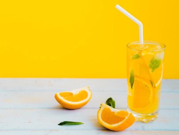 Exuberante vaso húmedo de zumo de naranja con menta Foto gratis