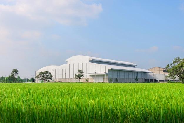 Fábrica en el medio de una tierra de cultivo verde en un día nublado Foto Premium
