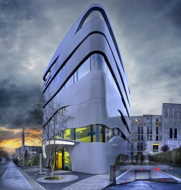 Fachada de un edificio moderno con ventanas geométricas y paredes curvas. Foto gratis