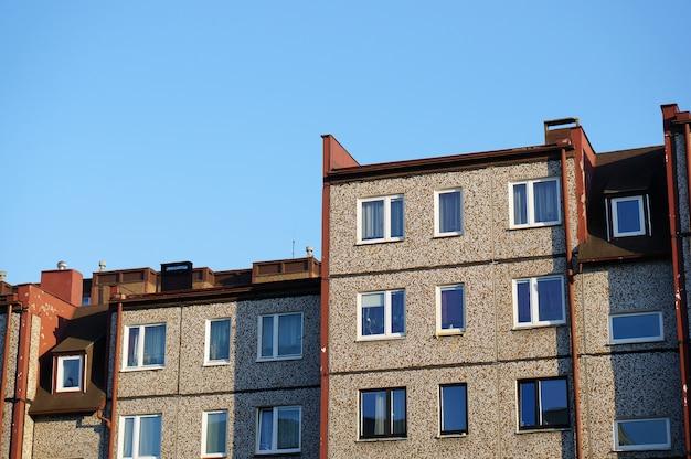Fachada de una hilera de edificios de apartamentos contra un cielo azul claro Foto gratis