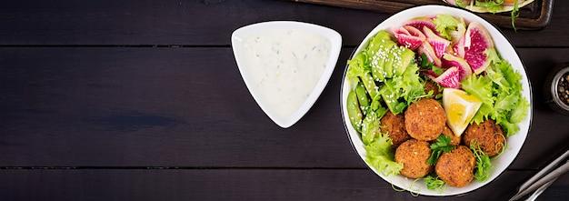 Falafel y verduras frescas. tazón de buda. oriente medio o platos árabes vista superior. bandera Foto gratis