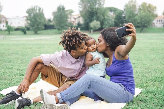 Familia africana feliz tomando una selfie con cámara de teléfono inteligente móvil en un parque público al aire libre Foto Premium