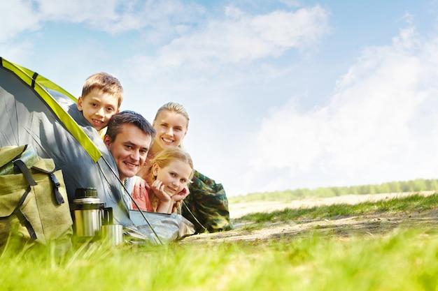 Familia alegre acampando en el parque Foto gratis