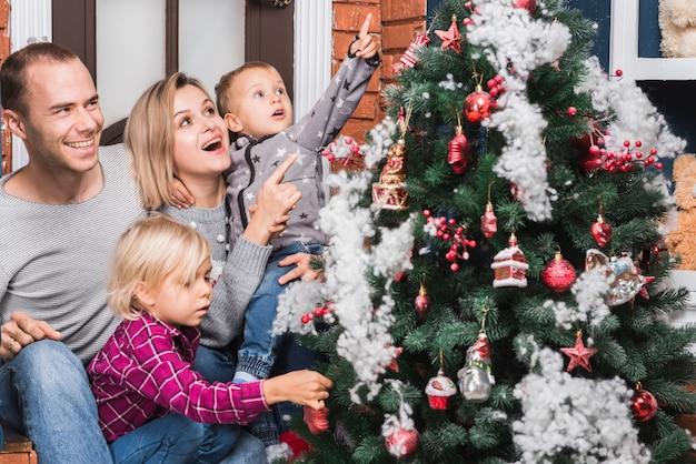 Familia alegre con árbol de navidad Foto gratis