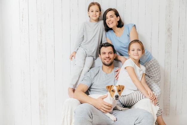 Familia amistosa posan juntos contra blancos: dos hermanitas, padre, madre y su mascota Foto Premium