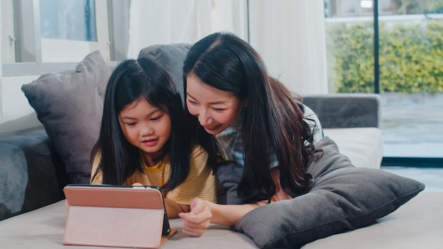 Familia asiática joven e hija felices usando la tableta en casa. madre japonesa relajarse con niña viendo la película acostado en el sofá en la sala de estar en casa. mamá divertida y niño encantador se divierten. Foto gratis