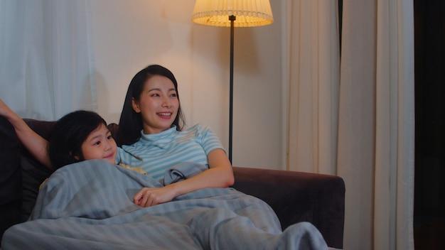 Familia asiática joven e hija viendo la televisión en casa en la noche. madre coreana con niña feliz usando el tiempo en familia relajarse tumbado en el sofá en la sala de estar. mamá divertida y niño encantador se divierten. Foto gratis