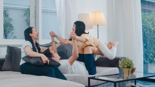 La familia asiática joven feliz juega junto en el sofá en casa. china madre padre e hija hijo disfrutando feliz relajarse pasar tiempo juntos en la moderna sala de estar en la noche. Foto gratis