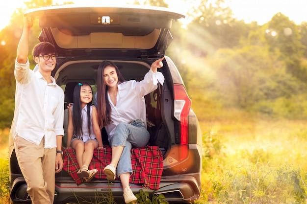 Familia asiática padre, madre e hija juegan juntos en el coche Foto Premium