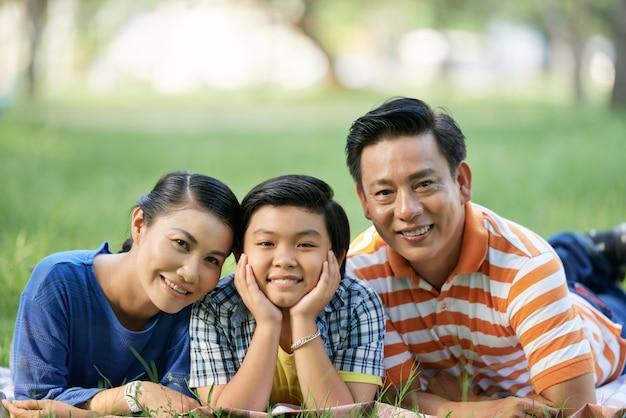 Familia asiática en el parque público verde Foto gratis