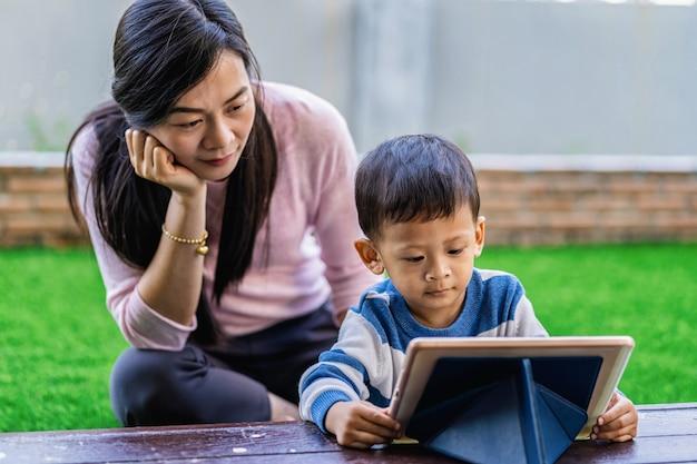 Familia asiática con su hijo está mirando la caricatura a través de la tableta de tecnología y jugando juntos Foto Premium