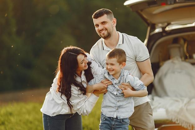 Familia en un bosque de verano junto al tronco abierto Foto gratis