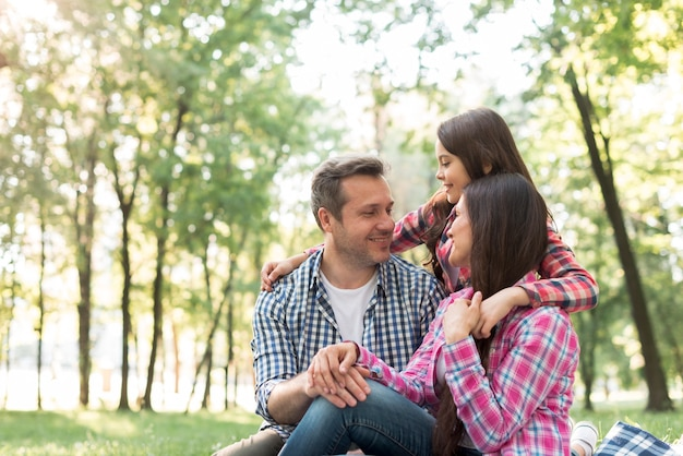 Familia cariñosa que se sienta en el parque que se mira Foto gratis