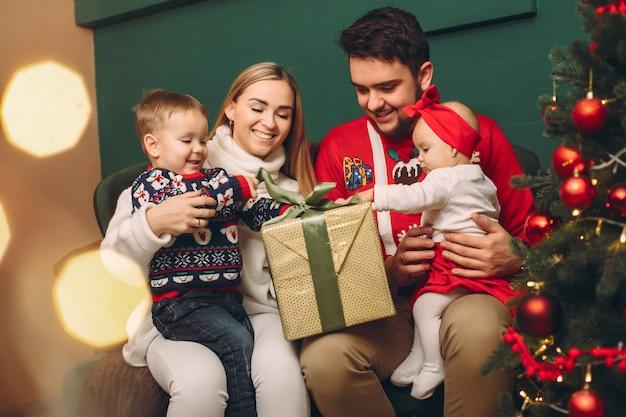 Familia en casa cerca del árbol de navidad Foto gratis