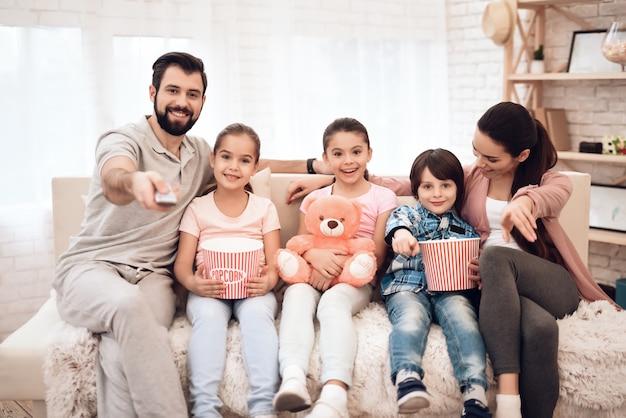 Una familia de cinco está sentada en el sofá de su departamento. Foto Premium