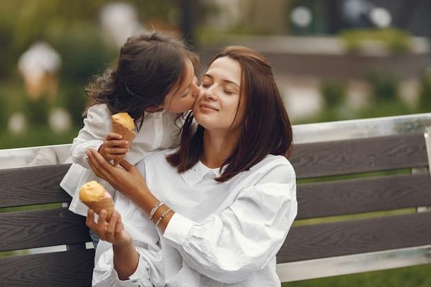 Familia en una ciudad. niña come helado. madre con hija sentada en un banco. Foto gratis