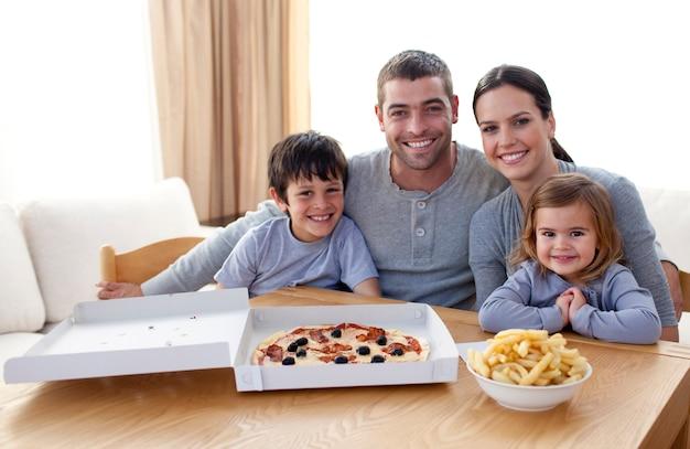 Familia Comiendo Pizza Y Papas Fritas En Casa