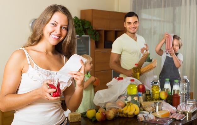 Familia de cuatro con bolsas de comida Foto gratis