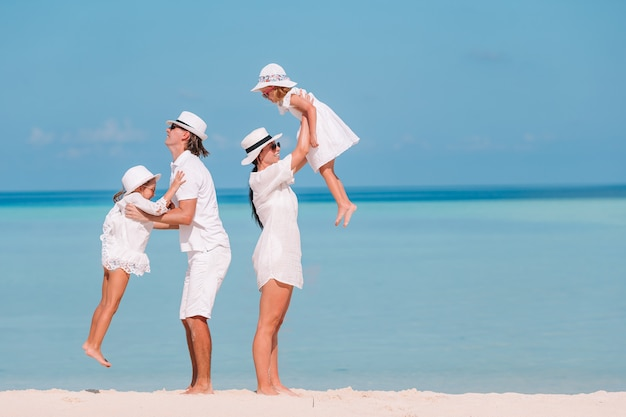 Familia de cuatro en vacaciones en la playa divertirse Foto Premium
