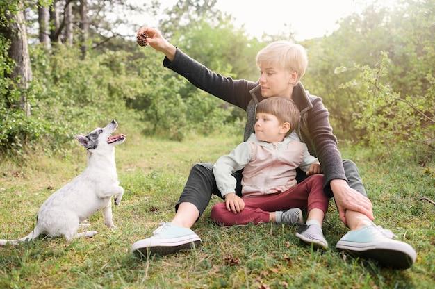 Familia disfrutando de la naturaleza con mascota Foto gratis
