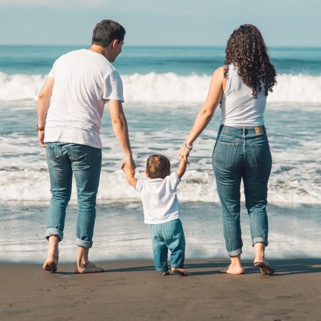 Familia feliz con el bebé caminando en la playa y mirando el mar Foto gratis