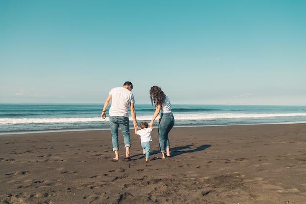 Familia feliz con el bebé divirtiéndose en la playa Foto gratis