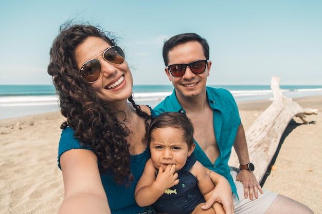 Familia feliz con el bebé tomando selfie en la playa en día de verano Foto gratis