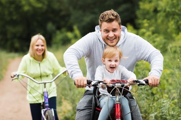 Familia feliz con bicicletas en camino forestal Foto gratis