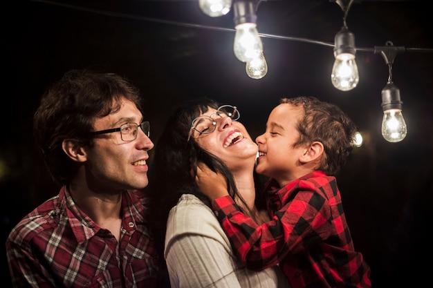 Familia feliz bajo bombillas sesión de fotos de navidad Foto gratis