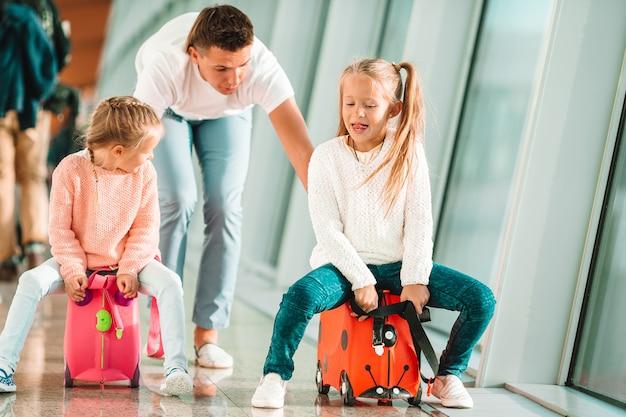 La familia feliz con dos niños en el aeropuerto se divierte esperando el embarque Foto Premium