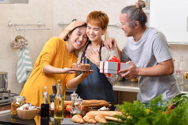 Familia feliz de madre padre e hija en la cocina celebrando la fiesta de cumpleaños junto con pastel y presente Foto Premium