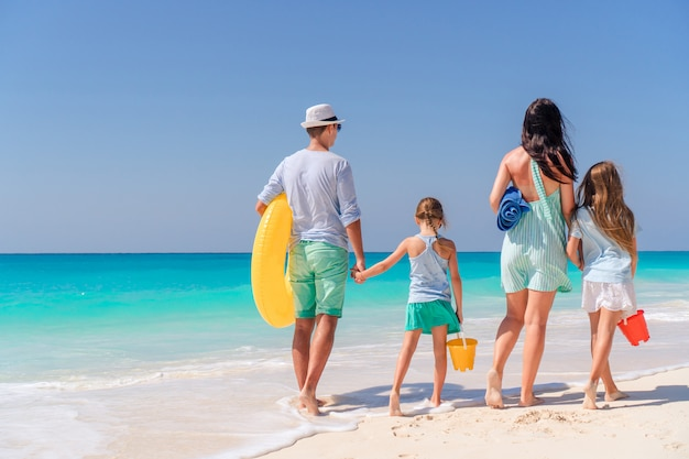 Familia feliz con niños a pie en la playa al atardecer Foto Premium